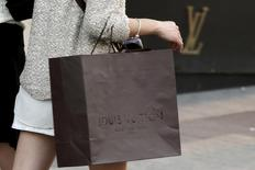 A woman walks with a Louis Vuitton shopping bag as she leaves a Louis Vuitton store in Paris September 24, 2013. This year Louis Vuitton's sales growth halved as it failed to anticipate consumers' move away from logo-branded luxury goods, Chinese demand cooled and it put the brake on expansion. Uncertainty about the brand's future growth heightened further when a source close to LVMH said on October 2, 2013 that Vuitton's star designer Marc Jacobs was leaving. To match Analysis LVMH-GROWTH/ Picture taken September 24, 2013.  REUTERS/Philippe Wojazer   (FRANCE - Tags: BUSINESS SOCIETY WEALTH FASHION) - RTR3FNG3