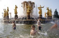 Мальчики купаются в фонтане на ВДНХ в Москве 16 июля 2010 года. Наступающие выходные в Москве будут жаркими и солнечными, ожидают синоптики. REUTERS/Denis Sinyakov