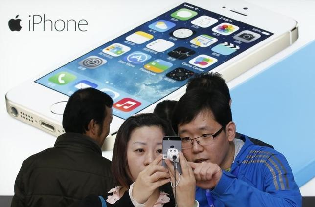 A staff of a China Mobile shop (R) explains a function of the iPhone 5s to a customer in Beijing January 17, 2014. REUTERS/Kim Kyung-Hoon/Files