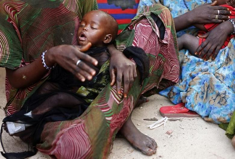 A woman holds her malnourished child in Sirlaabe IDP camp in Mogadishu June 28, 2012. REUTERS/Goran Tomasevic