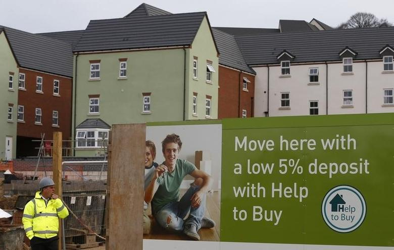 A builder stands by a ''help to buy'' advert on a Barratt Homes building site in Nuneaton, central England March 20, 2014.   REUTERS/Darren Staples