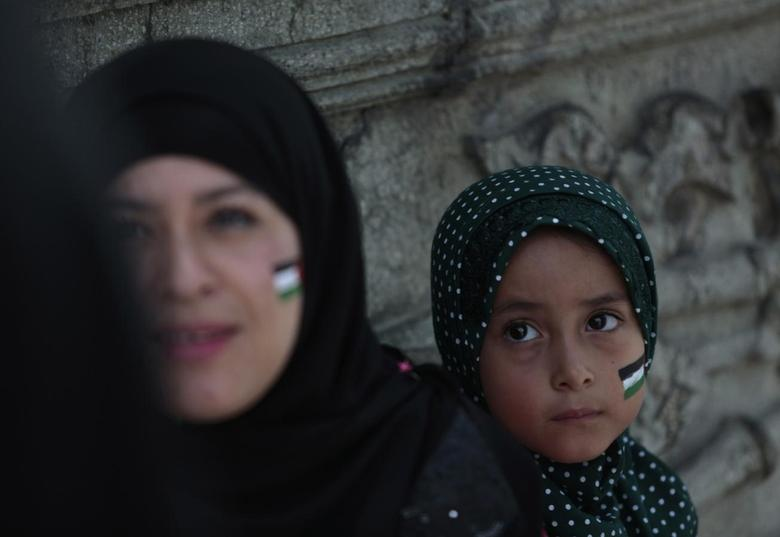 A woman and a child with the Palestinian flag painted on their faces are seen during a protest against the Israeli offensive on the Gaza Strip, in downtown Guatemala City, July 27, 2014. REUTERS/Jorge Dan Lopez