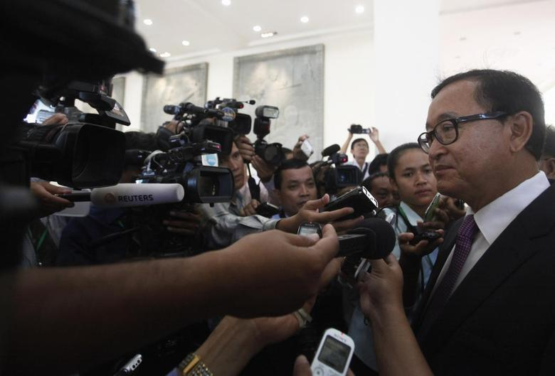 Sam Rainsy (R), president of the Cambodia National Rescue Party (CNRP), speaks to members of the media at Cambodia's National Assembly in central Phnom Penh July 28, 2014.  REUTERS/Samrang Pring