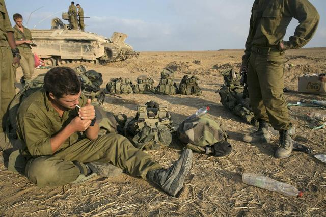 An Israeli soldier smokes a cigarette after crossing back into Israel from Gaza July 28, 2014. REUTERS/Baz Ratner