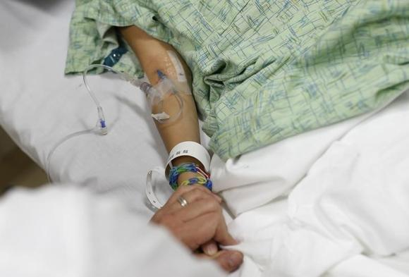 A doctor holds the hand of a patient in a hospital in Peoria, Illinois.  REUTERS/Jim Young