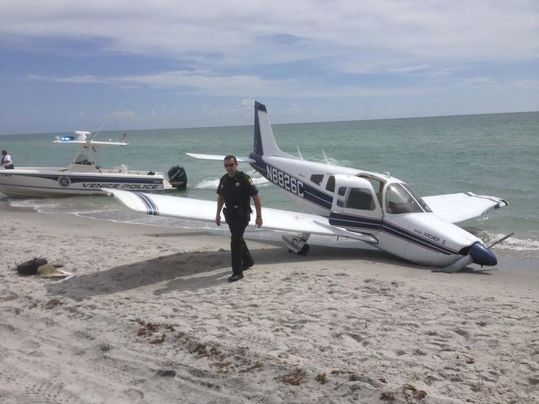 First responders respond at the scene of a single engine Piper Cherokee plane crash in this photo provided by the Sarasota County Sheriff's Office in Caspersen Beach in Venice, Florida July 27, 2014. REUTERS/Sarasota County Sheriff's Office/Handout