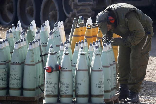 A Israeli soldier looks at shells next to a mobile artillery unit outside the Gaza Strip July 28, 2014. REUTERS/Baz Ratner