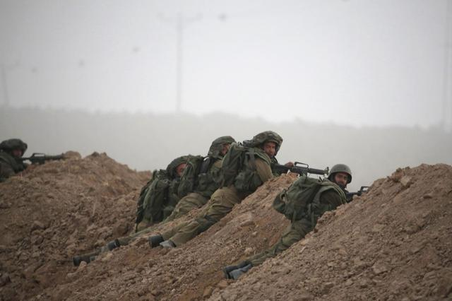 Israeli soldiers take positions near Kibbutz Nahal Oz, outside the northern Gaza Strip, during a gun battle July 28, 2014.  REUTERS/Baz Ratner