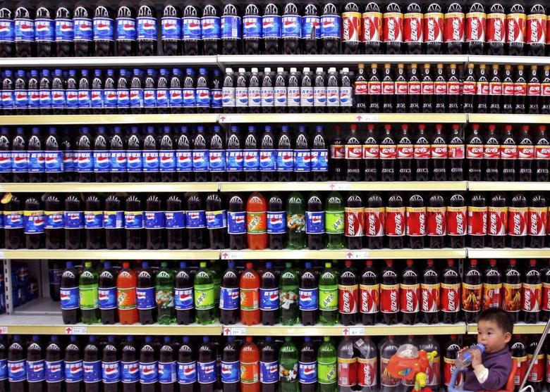 A boy sitting in a toy tricycle is pushed past shelves of bottled beverages at a supermarket in Nanjing, east China's Jiangsu province in this April 10, 2006 file photo. REUTERS/Stringer/Files