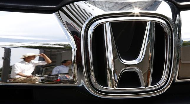 Man are reflected on a Honda Motor car outside the company showroom in Tokyo July 29, 2014.  Honda Motor Co's April-June operating profit rose 7.1 percent from a year earlier to 198.04 billion yen ($1.94 billion), beating analyst estimates, boosted by cost cuts and strong sales of the remodelled Fit in Japan  REUTERS/Toru Hanai (JAPAN - Tags: BUSINESS TRANSPORT)