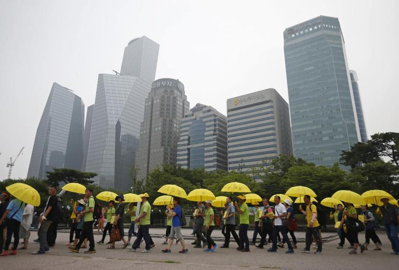 People holding yellow umbrellas in support of victims of the mid-April Sewol ferry disaster, carry boxes containing signatures of South Koreans petitioning for the enactment of a special law after the disaster, as they march towards the National Assembly at Yeouido Park in Seoul July 15, 2014.    REUTERS/Kim Hong-Ji