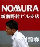 Мужчина проходит мимо логотипа Nomura Securities в Токио 25 июля 2013 года. Прибыль Nomura Holdings Inc снизилась второй квартал подряд, поскольку прекращение прошлогоднего ралли токийского фондового рынка негативно отразилось на брокерских комиссиях. REUTERS/Yuya Shino
