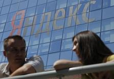 Люди на фоне логотипа Яндекса в Москве 23 мая 2014 года. Крупнейший российский интернет-поисковик Яндекс сократил чистую прибыль во втором квартале 2014 года из-за убытка от курсовых разниц, но нарастил выручку благодаря росту доходов от рекламы и подтвердил прогноз на 2014 год. REUTERS/Maxim Shemetov