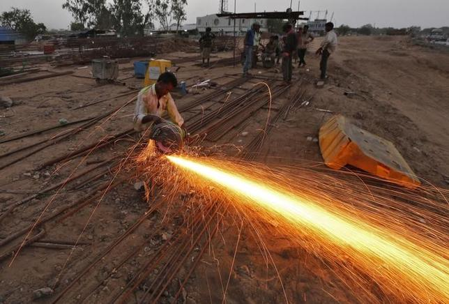 A labourer cuts an iron rod at the construction site of a flyover on the outskirts of Ahmedabad June 24, 2014. REUTERS/Amit Dave/Files