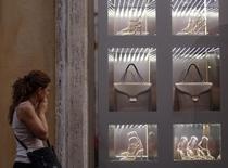A woman walks past a shop window in downtown Rome August 2, 2011. REUTERS/Tony Gentile