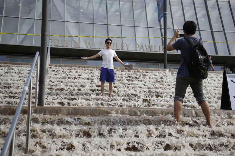 A man poses for a photo on stairs to a parking structure outside UCLA's Pauley Pavilion sporting arena as water flows down from a broken thirty inch water main that was gushing water onto Sunset Boulevard near the UCLA campus in the Westwood section of Los Angeles July 29, 2014. REUTERS/Danny Moloshok