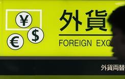 Мужчина проходит мимо пункта обмена валюты в аэропорту Ханэда в Токио 1 августа 2011 года. Курс доллара близок к 10-месячному пику к корзине основных валют за счет экономического роста в США. REUTERS/Yuriko Nakao