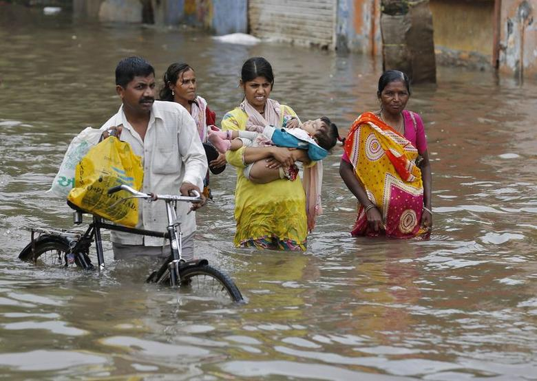 A woman carries her child as she wades through a flooded street with others after heavy monsoon rains in Ahmedabad July 30, 2014. REUTERS/Amit Dave