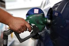 Работник АЗС компании PDVSA заправляет автомобиль в Каракасе 16 декабря 2013 года. Аналитики повысили прогноз цены на нефть Brent в 2014 и 2015 годах с учетом геополитических рисков. REUTERS/Carlos Garcia Rawlins