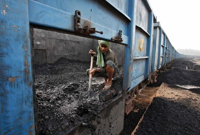 A worker unloads coal from a goods train at a railway yard in Chandigarh July 8, 2014. REUTERS/Ajay Verma