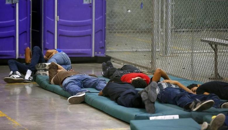 Young boys sleep in a holding cell where hundreds of mostly Central American immigrant children are being processed and held at the U.S. Customs and Border Protection Nogales Placement Center in Nogales, Arizona June 18, 2014.  REUTERS/Ross D. Franklin/Pool