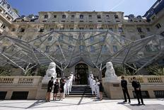 Employees pose on the steps outside the Peninsula Paris luxury hotel during a press presentation in Paris in this June 24, 2014 file picture.  REUTERS/Benoit Tessier/Files