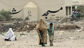 An internally displaced woman walks outside a food distribution centre set up in a sports stadium in Bannu, in northwest Pakistan July 25, 2014. REUTERS/Caren Firouz