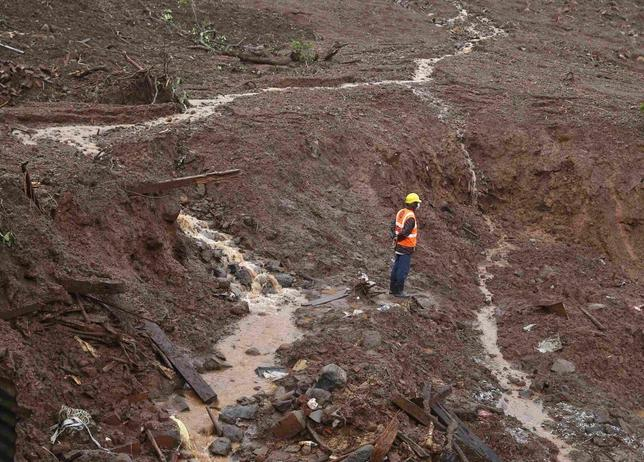 A National Disaster Response Force (NDRF) personnel stands at the site of a landslide at Malin village in the western Indian state of Maharashtra August 1, 2014.  REUTERS/Shailesh Andrade