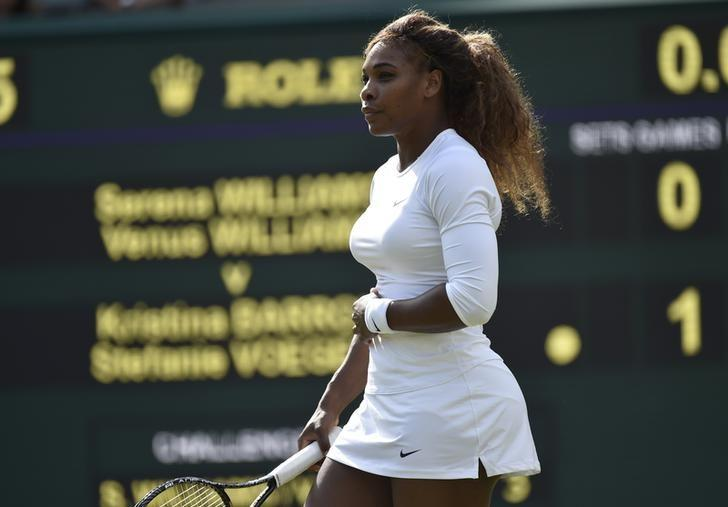 Serena Williams of the U.S. holds her stomach before retiring from her women's doubles tennis match with Venus Williams of the U.S. against Kristina Barrois of Germany and Stefanie Voegele of Switzerland at the Wimbledon Tennis Championships, in London July 1, 2014.          REUTERS/Toby Melville
