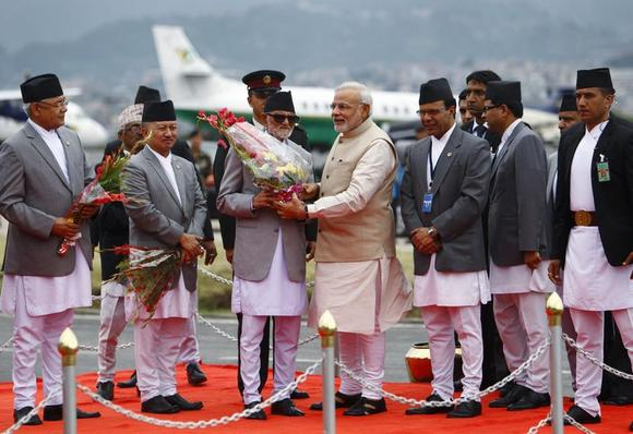 Prime Minister Narendra Modi (C) receives a bouquet from his Nepalese counterpart Sushil Koirala upon his arrival at Tribhuvan International Airport in Kathmandu August 3, 2014. REUTERS/Navesh Chitrakar