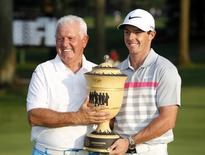 Aug 3, 2014; Akron, OH, USA; Rory McIlroy (right) and his father Gerry McIlroy following the final round of the WGC-Bridgestone Invitational golf tournament at Firestone Country Club - South Course.  Joe Maiorana-USA TODAY Sports