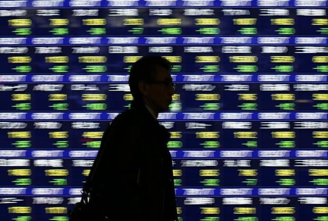 A man walks past an electronic stock quotation board outside a brokerage in Tokyo January 14, 2014. REUTERS/Issei Kato/Files