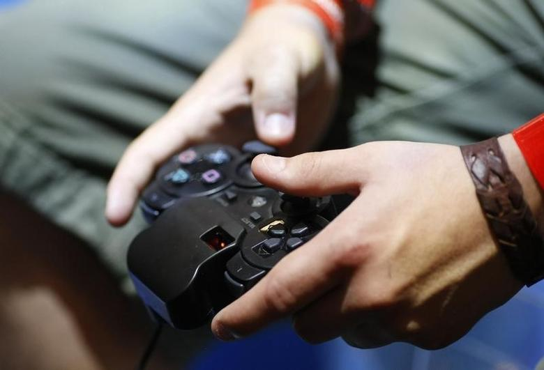 A visitor plays with a 'Playstation' at an exhibition stand at the Gamescom 2009 fair in Cologne August 22, 2009. REUTERS/Ina FAssbender