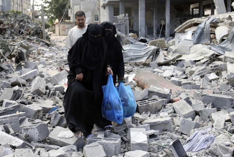 Palestinian women walk upon the debris of a house which witnesses said was destroyed in an Israeli air strike, in Rafah in the southern Gaza Strip August 4, 2014.  REUTERS/Ibraheem Abu Mustafa