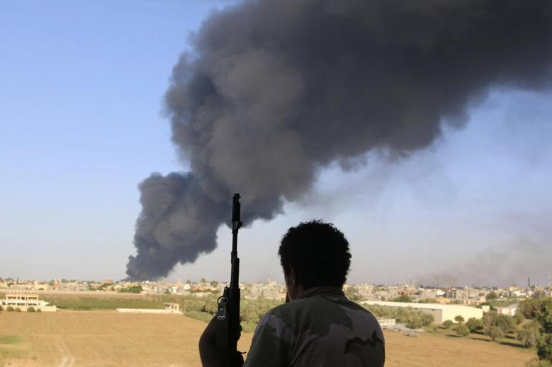 A fighter from Zintan brigade watches as smoke rises after rockets fired by one of Libya's militias struck and ignited a fuel tank in Tripoli August 2, 2014.   REUTERS/Hani Amara