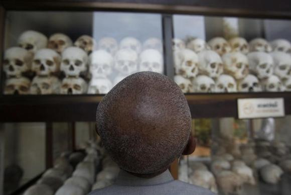 A man looks at skulls and bones of more than 8,000 victims of the Khmer Rouge regime at Choeung Ek, a ''Killing Fields'' site located on the outskirts of Phnom Penh April 17, 2014. REUTERS/Samrang Pring/Files