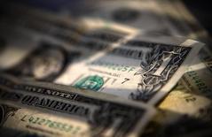 Долларовые купюры в Торонто 26 декабря 2008 года. Доллар во вторник держится ниже 10,5-месячного пика к корзине валют, взяв паузу после того, как данные о занятости в США на прошлой неделе приглушили слухи о более раннем, чем ожидалось, повышении ключевой ставки ФРС. REUTERS/Mark Blinch