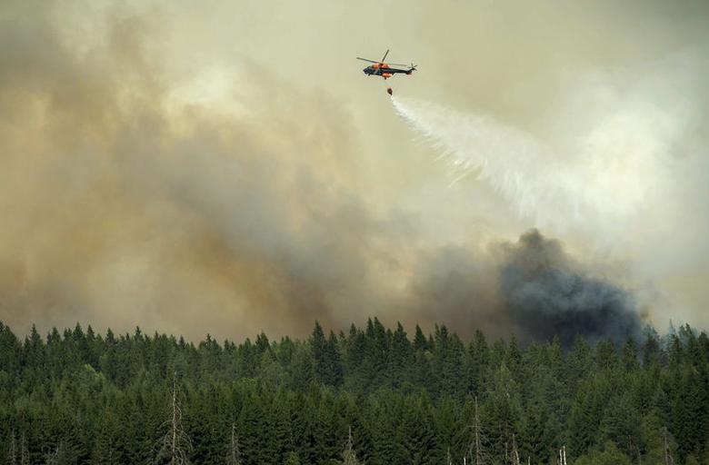 A helicopter dumps its load of water on the wildfire front just outside the evacuated village of Gammelby near Sala, central Sweden August 4, 2014.  REUTERS/Fredrik Sanberg/TT News Agency