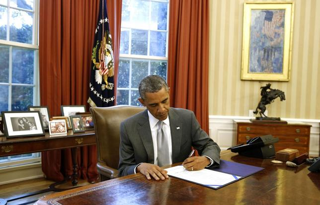 U.S. President Barack Obama signs H.J. Res. 76, Emergency Supplemental Appropriations Resolution, 2014, to provide funding to Israel for the Iron Dome defense system to counter short-range rocket threats while in the Oval Office in the White House in Washington, August 4, 2014.     REUTERS/Larry Downing