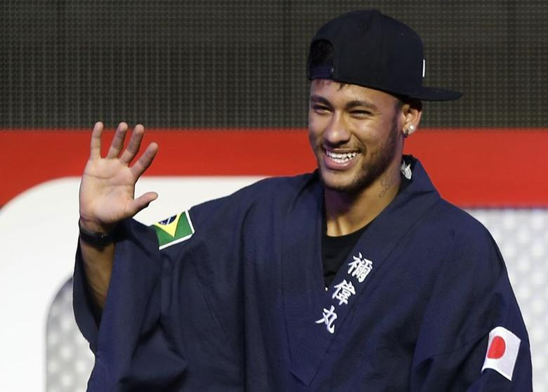 Brazilian soccer player and Barcelona forward Neymar waves as he wears a ''Yukata'', a casual summer Kimono, after receiving it as a souvenir from the organizer during a fan event in Tokyo July 31, 2014.  REUTERS/Yuya Shino