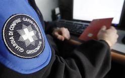 Швейцарский пограничник проверяет паспорт в аэропорту Базель-Мюльхаус 7 февраля 2012 года. Власти Швейцарии расширили список лиц и компаний, которым создали препятствия для обхода антироссийских санкций Запада. REUTERS/Pascal Lauener