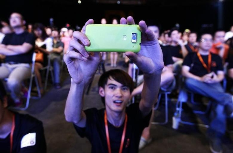 A user of Xiaomi uses his mobile phone to take a photo at a launch ceremony of Xiaomi Phone 2 in Beijing August 16, 2012. REUTERS/Jason Lee/Files