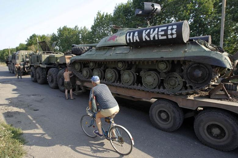A man rides a bicycle past Ukrainian servicemen who are transporting a JS-3 (IS-3) World War Two tank seized from pro-Russian separatists in the eastern Ukrainian town of Kramatorsk August 1, 2014. REUTERS/Valentyn Ogirenko