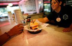Una mesera sirve una hamburguesa en el restaurante Cheeburger Cheeburger de Coral Spring, EEUU, jul 28 2008. El ritmo del crecimiento del sector servicios de Estados Unidos marcó en julio su máximo nivel en ocho años y medio, impulsado por la expansión de la actividad de negocios, los nuevos pedidos y el empleo, de acuerdo con un reporte sectorial publicado el martes.   REUTERS/Carlos Barria