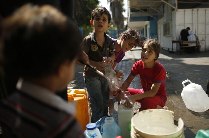Palestinian children, who fled their houses during an Israeli offensive, fill bottles with water at a United Nations-run school, sheltering displaced Palestinians, in Gaza City July 23, 2014.  Picture taken July 23, 2014.  REUTERS/Mohammed Salem