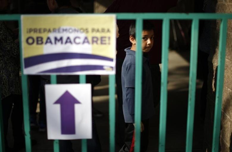 A boy waits in line at a health insurance enrollment event in Cudahy, California March 27, 2014. REUTERS/Lucy Nicholson