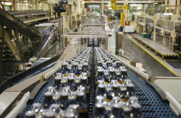Bottles of soft drinks made by drinks company Britvic sit on a conveyor belt at  Britvic's bottling plant in London March 25, 2009.    REUTERS/Luke MacGregor/Files