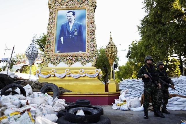 Thai soldiers take position in front of a picture of Thailand's King Bhumibol Adulyadej as their unit dismantles an anti-government encampment in central Bangkok May 23, 2014.  REUTERS/Damir Sagolj