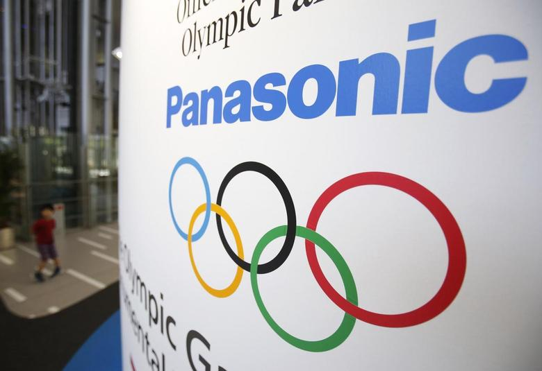 A Panasonic Corp logo and an Olympic symbol are seen as a kid walks past at Panasonic centre in Tokyo August 6, 2014.  REUTERS/Yuya Shino