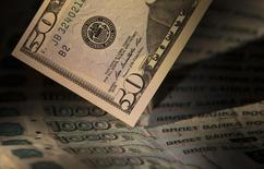 Купюры валют доллар США и рубль в Москве 17 февраля 2014 года. Рубль в среду упал на минимумы 4,5 месяцев, а доллар ушел выше отметки 36,25 из-за бегства от риска в связи с кризисом на Украине. REUTERS/Maxim Shemetov